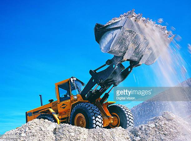 Backhoe lifting rubble