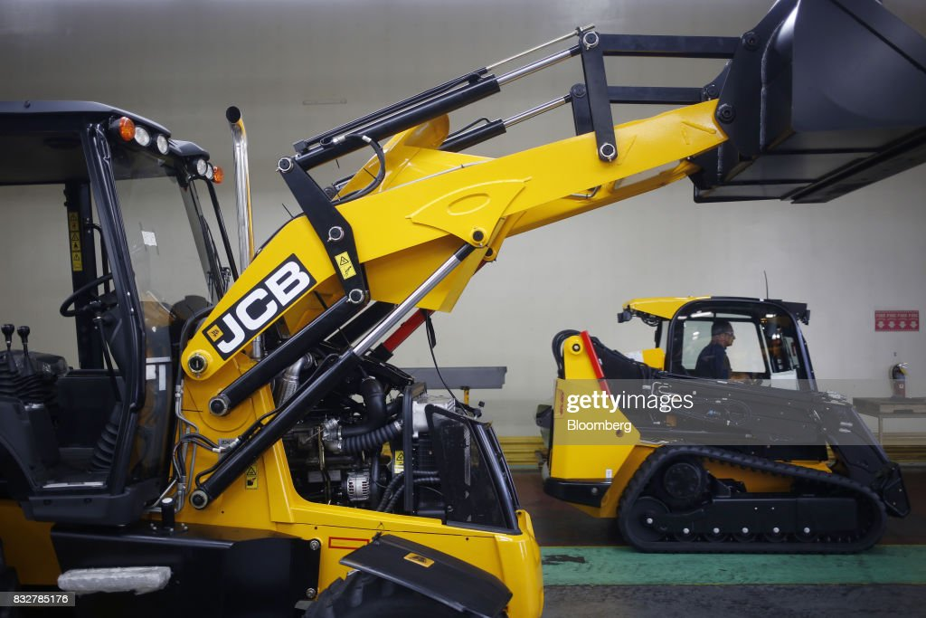 A backhoe loader construction vehicle sits in front of a track loader at the JC Bamford Excavators LTD. (JCB) manufacturing plant in Pooler, Georgia, U.S., on Friday, Aug. 11, 2017. The Federal Reserve is scheduled to release industrial production figures on August 17. Photographer: Luke Sharrett/Bloomberg via Getty Images