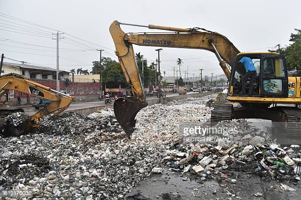 A backhoe loader removes garbage to clean the canal of Portail Leogane in the Haitian capital of PortauPrince on October 3 2016 Hurricane Matthew...