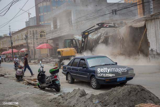 A backhoe loader seen destroying traditional homes to build newly houses in the streets of Keriya in the Hotan Prefecture Xinjiang Uyghur Autonomous...