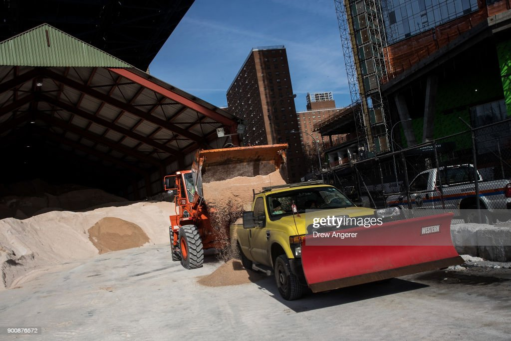 A backhoe loads a New York City Department of Transportation truck with road salt at a storage depot on the Lower East Side, January 3, 2018 in New York City. New York City was placed under a winter storm watch Wednesday as a major weather system is expected to threaten the area with heavy snow and powerful wind Wednesday night into Thursday.