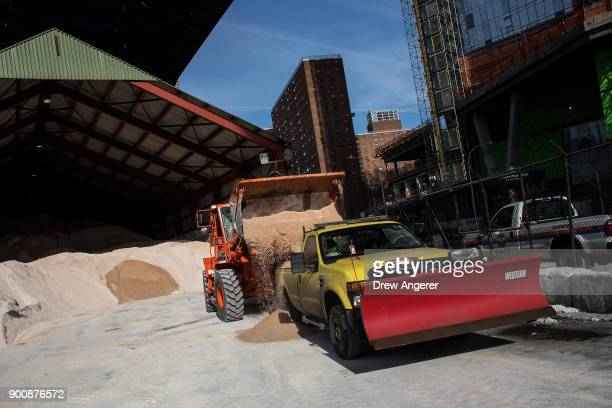 A backhoe loads a New York City Department of Transportation truck with road salt at a storage depot on the Lower East Side January 3 2018 in New...