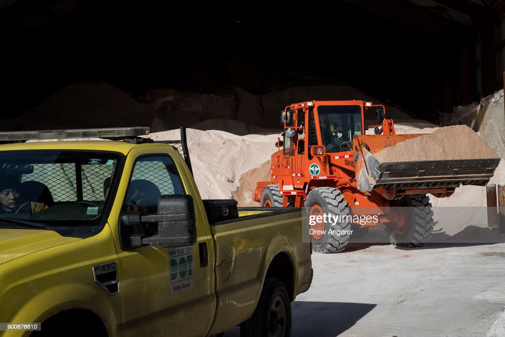 A backhoe prepares to load a New York City Department of Transportation truck with road salt at a storage depot on the Lower East Side, January 3, 2018 in New York City. New York City was placed under a winter storm watch Wednesday as a major weather system is expected to threaten the area with heavy snow and powerful wind Wednesday night into Thursday.