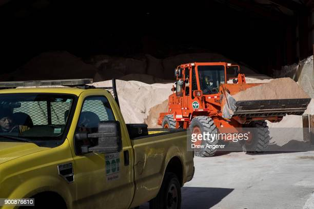 A backhoe prepares to load a New York City Department of Transportation truck with road salt at a storage depot on the Lower East Side January 3 2018...