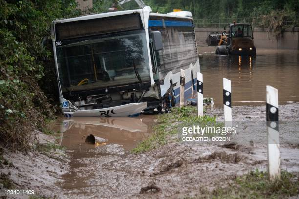Backhoe removes mud behind a bus in Euskirchen, western Germany, on July 16 after heavy rain hit parts of the country, causing widespread flooding. -...