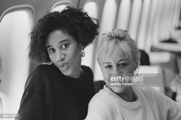 Backing singers Pepsi and Shirlie on board an airliner during 'The Big Tour', with British pop duo Wham!, 1985. Left to right: Helen DeMacque and...