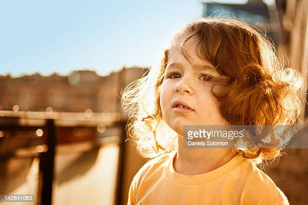 Backlight boy with curly long hair