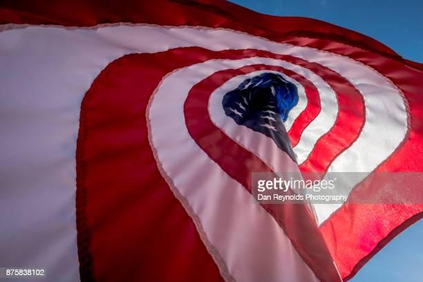 backlit american flag blowing in wind - veterans day parade stock photos and pictures