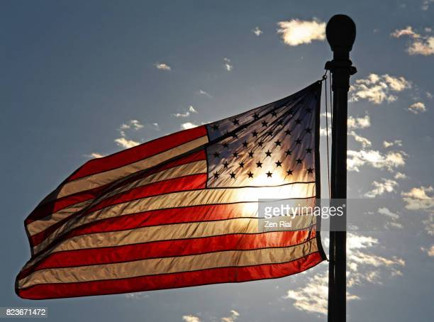 backlit american flag on flag pole against the sky - independence day stock pictures, royalty-free photos & images