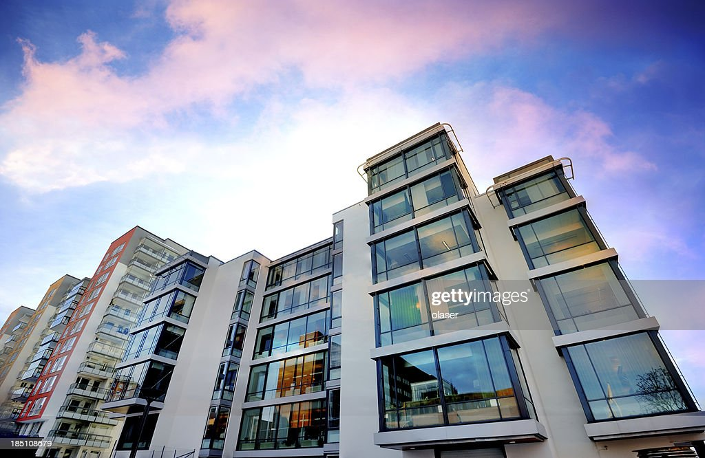 Backlit apartment building against dramatic sky : Stock Photo