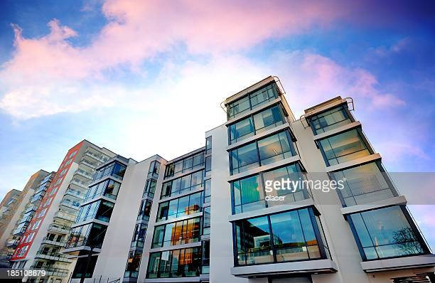backlit apartment building against dramatic sky - flat stock pictures, royalty-free photos & images
