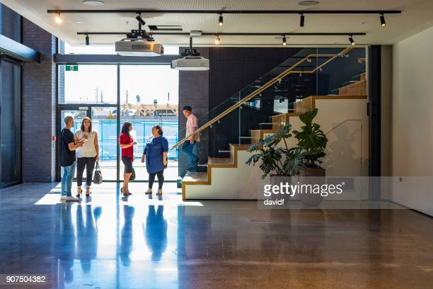 Backlit Business People Walking Through an Office Lobby
