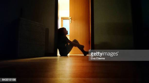 backlit child sitting in a dark doorway in contemplation - kindertijd stockfoto's en -beelden