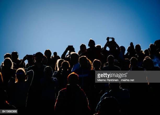 Backlit crowd spectating an outdoors event under a clear blue sky
