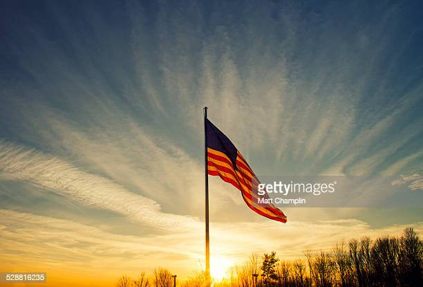 backlit flying american flag - patriotism stock photos and pictures