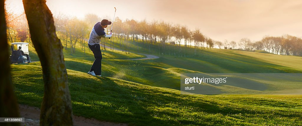 backlit golf course with golfer chipping onto green : Stock Photo