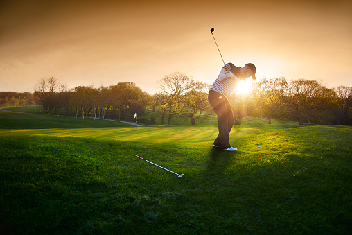 backlit golf course with golfer chipping onto green 481358874