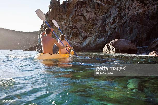 A back-lit man and a woman kayak into a rocky cove on the island of St. John, USVI.