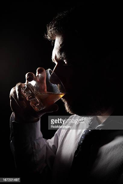 Backlit man drinking alcohol from barware