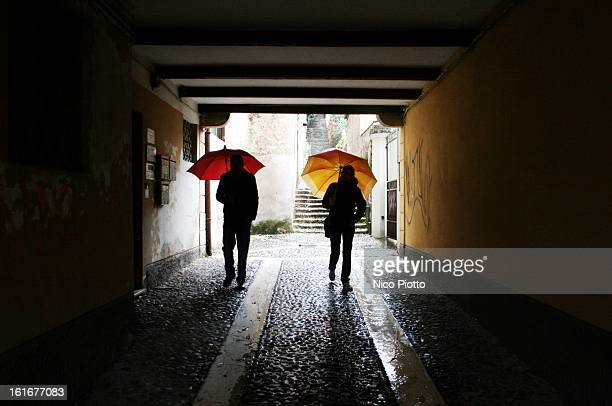 Backlit of couple with their coloured umbrella walking in the morning in Schio in October 2012. Schio, Vicenza, Italy.