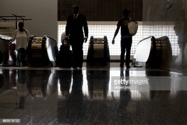 Backlit passersby at an escalator at HartsfieldJackson Atlanta International Airport
