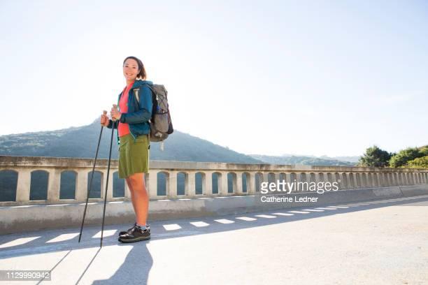 Backlit portrait of fit woman on bridge with walking sticks
