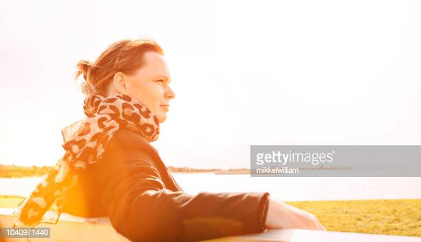 Backlit portrait of woman with scarf in her late 30s shot outside