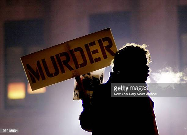 A backlit protestor holds a sign outside the Albany County Courthouse where the trial of four New York City police officers in the shooting death of...