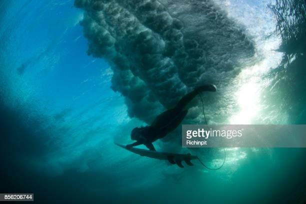 Backlit surfer girl duckdives