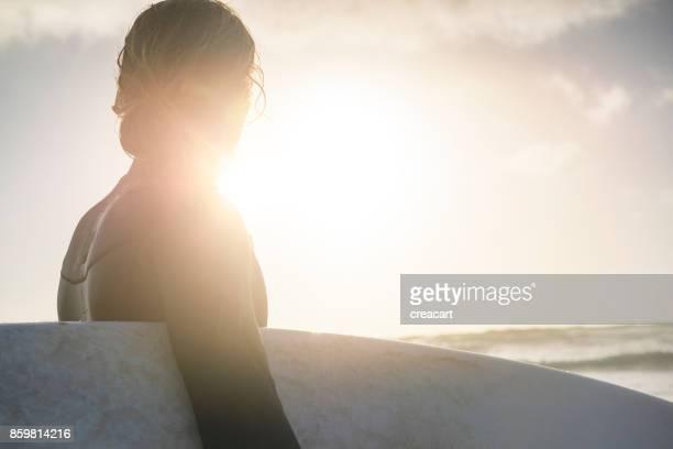 backlit surfer holding surfboard, with sunset lens flare