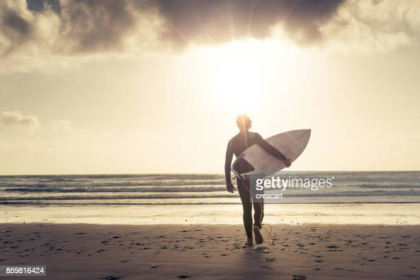 Backlit surfer walking into the sea at Sunset, Newquay, Cornwall.