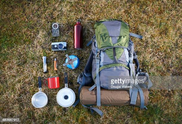 Backpack and camping equipment on grass.