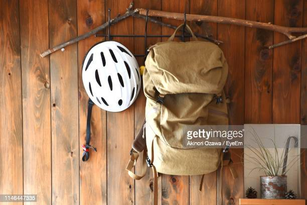backpack and cycling helmet hanging on wooden wall - hanging stock pictures, royalty-free photos & images