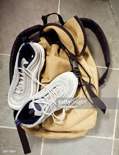 A backpack and gym shoes on a tile floor