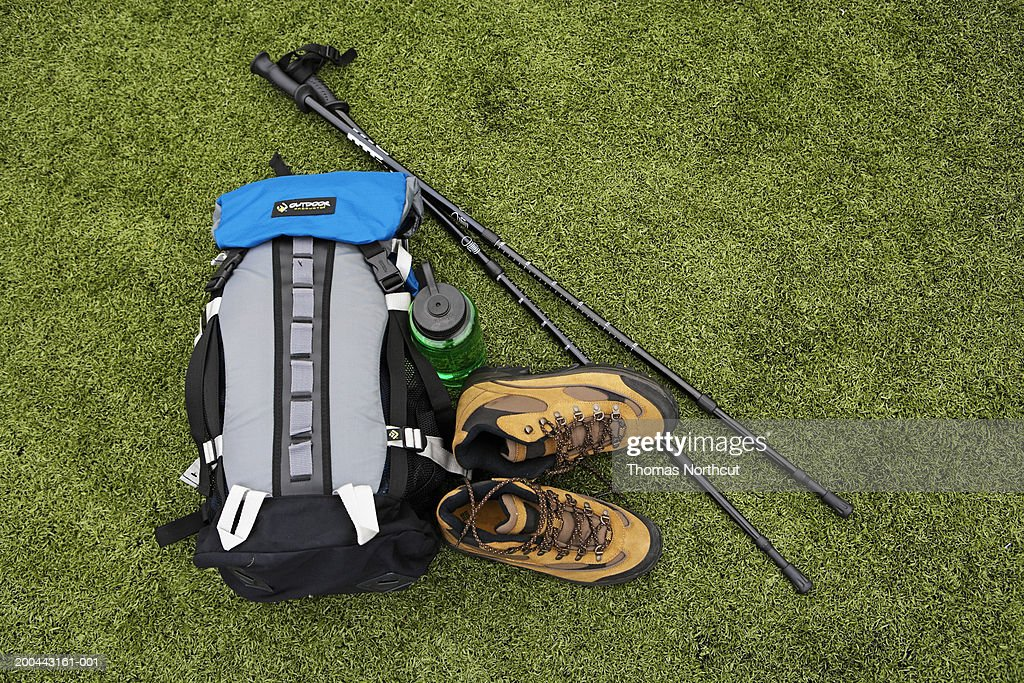 Backpack, hiking boots, water bottle and hiking pole on turf : Stock Photo