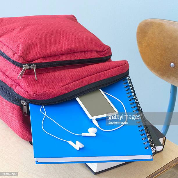 backpack, notebooks, and mp3 player on school desk - satchel bag stock photos and pictures
