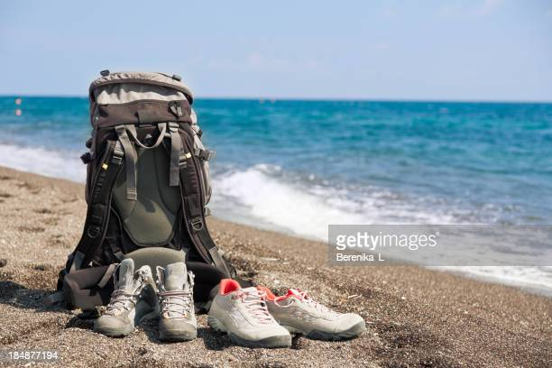 Backpack on beach surrounded by two Paris of sneakers