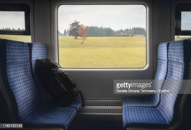 backpack on vehicle seat by window in train - passenger train stock pictures, royalty-free photos & images