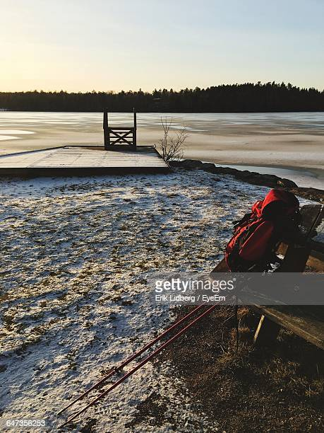 Backpack With Hiking Pole On Bench At Field During Winter