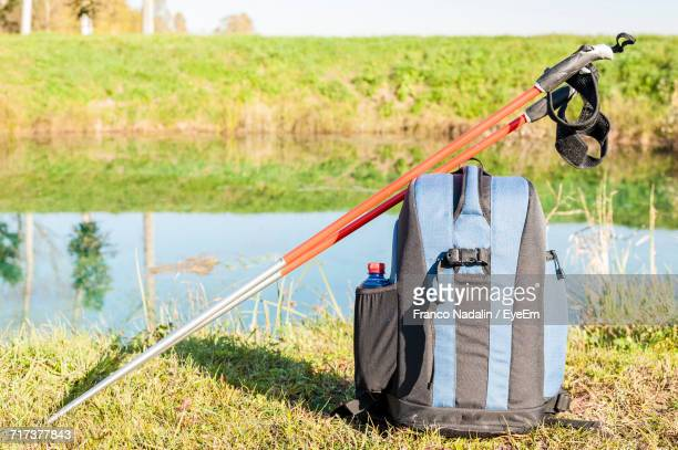 Backpack With Hiking Poles At Lakeshore During Sunny Day