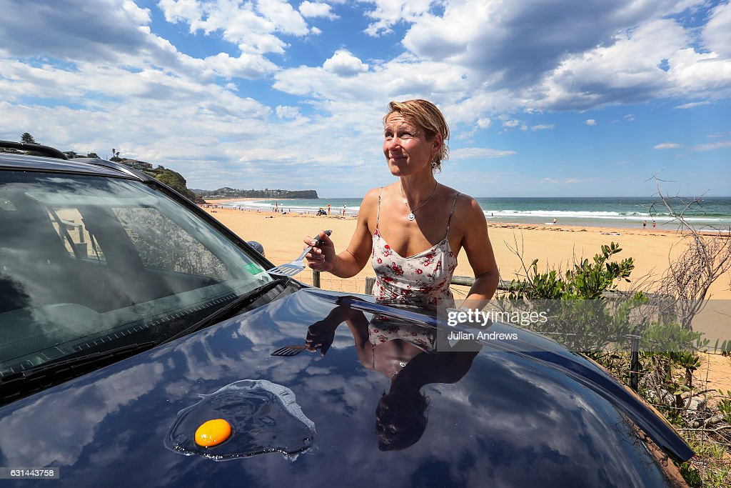 Backpacker Anna Bole from Latvia attempts to cook an egg on the bonnet of her car at Warriewood Beach on January 11, 2017 in Sydney, Australia. High temperatures combined with rising humidity have made for an uncomfortable day in Sydney, with temperatures hitting 40 degrees Celsius in some parts.