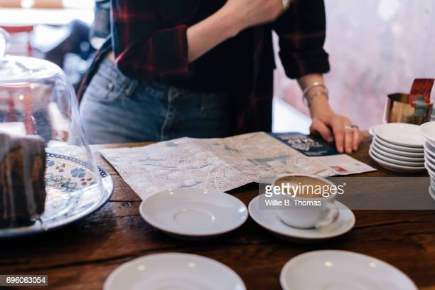 Backpacker Checking Route As She Orders Coffee At Cafe Counter'n