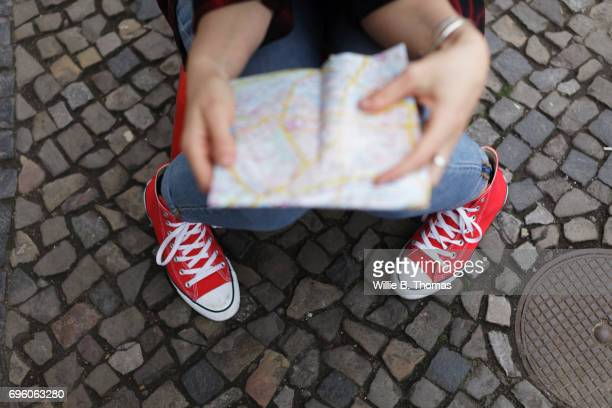 A Backpacker Checks Her Map In The Street