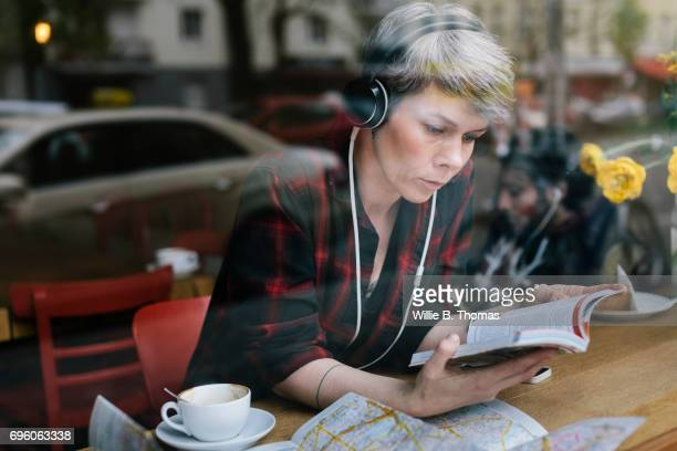 A Backpacker Checks The Local Points Of Interest At A Cafe