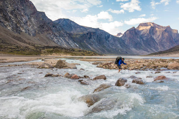 Backpacker crosses cold, rushing river on Baffin Island