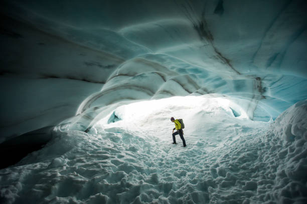 Backpacker explores the inside a glacial ice cave.