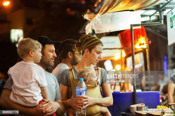 Backpacker family with children at street kitchen in Khao San