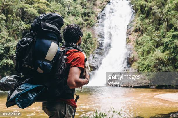 backpacker hiker looking at a waterfall - south america stock pictures, royalty-free photos & images