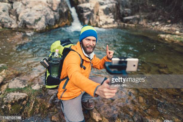 backpacker hiking and vlogging - photo messaging stock pictures, royalty-free photos & images