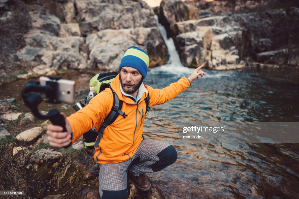 Backpacker hiking and vlogging : Stock Photo